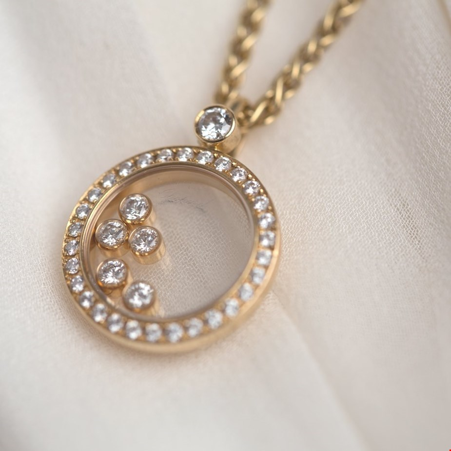 Xupes pre-owned Chopard yellow gold happy diamonds necklace placed on a wedding dress