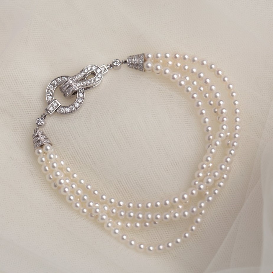 Xupes pre-owned cartier diamond and pearl bracelet placed on a bridal veil