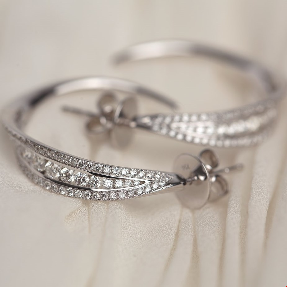 Xupes pre-owned Mappin and Webb white gold diamond hoop earrings placed on a wedding dress