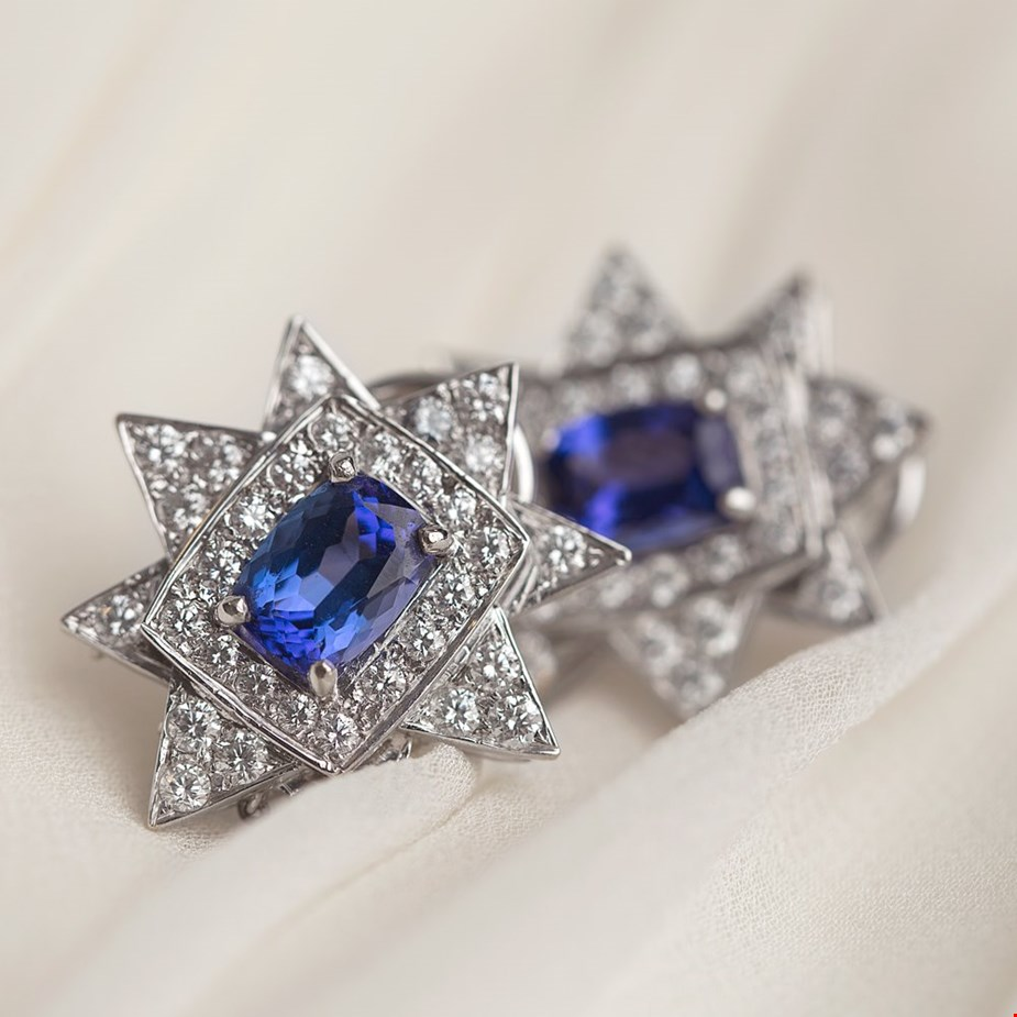 Xupes pre-owned tanzanite white gold diamond earrings placed on a wedding dress