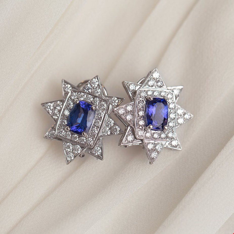 Xupes pre-owned tanzanite white gold diamond earrings placed on a wedding dres