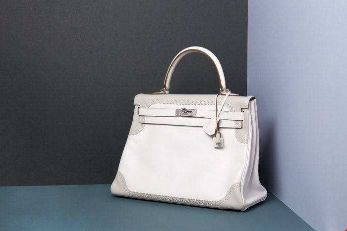 Xupes pre-owned Hermes Kelly placed on a coloured background