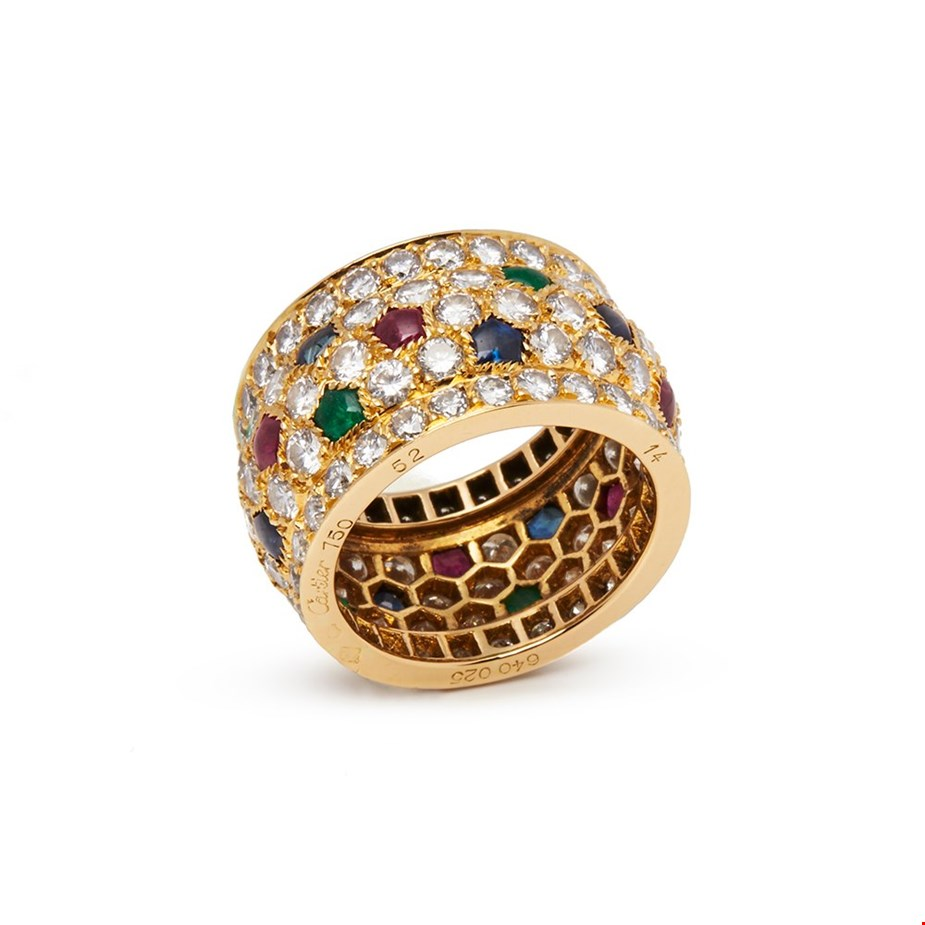 This pre-owned Cartier ring is from their Nigeria collection and features round brilliant cut Diamonds with cabochon cut Sapphires, Rubies and Emeralds, made in 18k Yellow Gold.