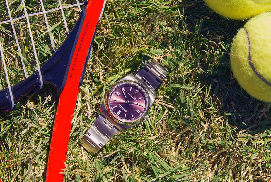 Xupes pre-owned rolex oyster perpetual placed on the grass next to a tennis racket and tennis balls