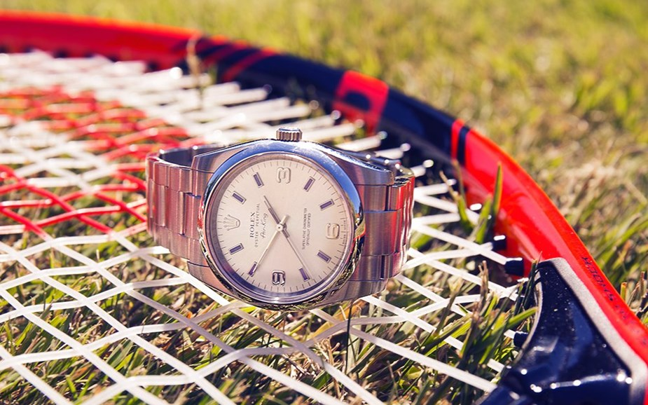 xupes pre-owned rolex air king placed on a tennis racket