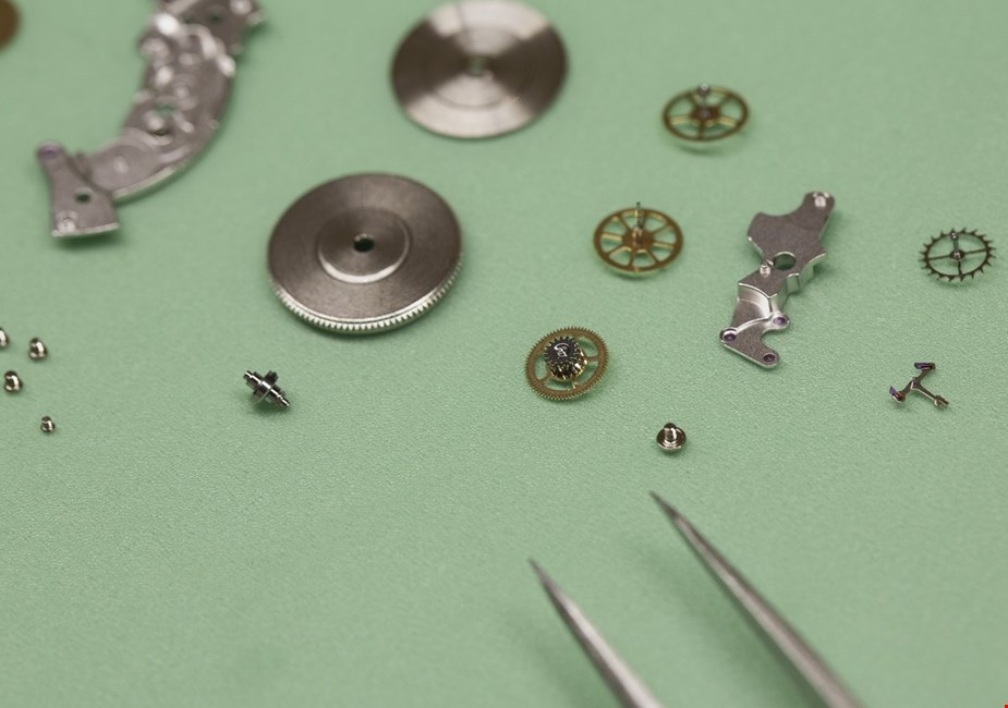 various cartier watch movement parts on a workbench